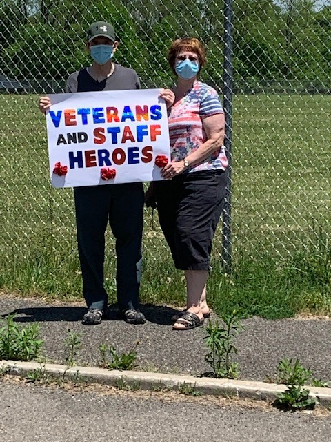 Event attendees hold a sign thanking veterans